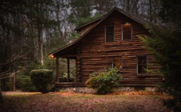 Brunt træhus ude i skoven med lys fra vinduerne