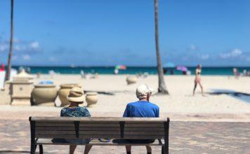 Gammel mand og dame sidder på bænk i udlandet