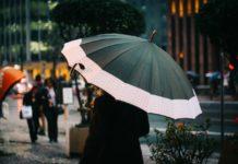 Kvinde går med paraply i byen