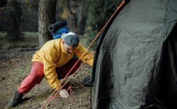 Mand er i gang med at sætte telt op